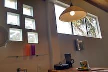 Pequena cozinha. Pia,frigobar, sanduicheira e cafeteira.