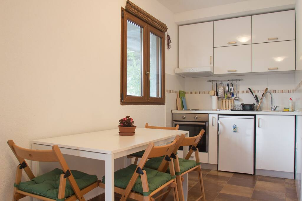 Kitchen and dining room with big table for 4 persons