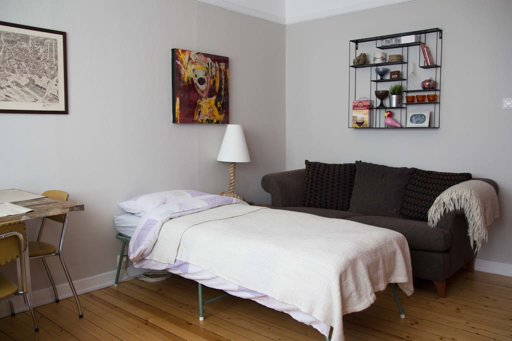 Fold up bed for my guests with a side table and reading lamp.