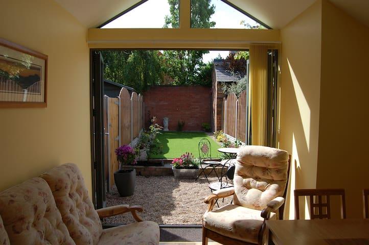 Sunroom with bi folding doors leading to garden.