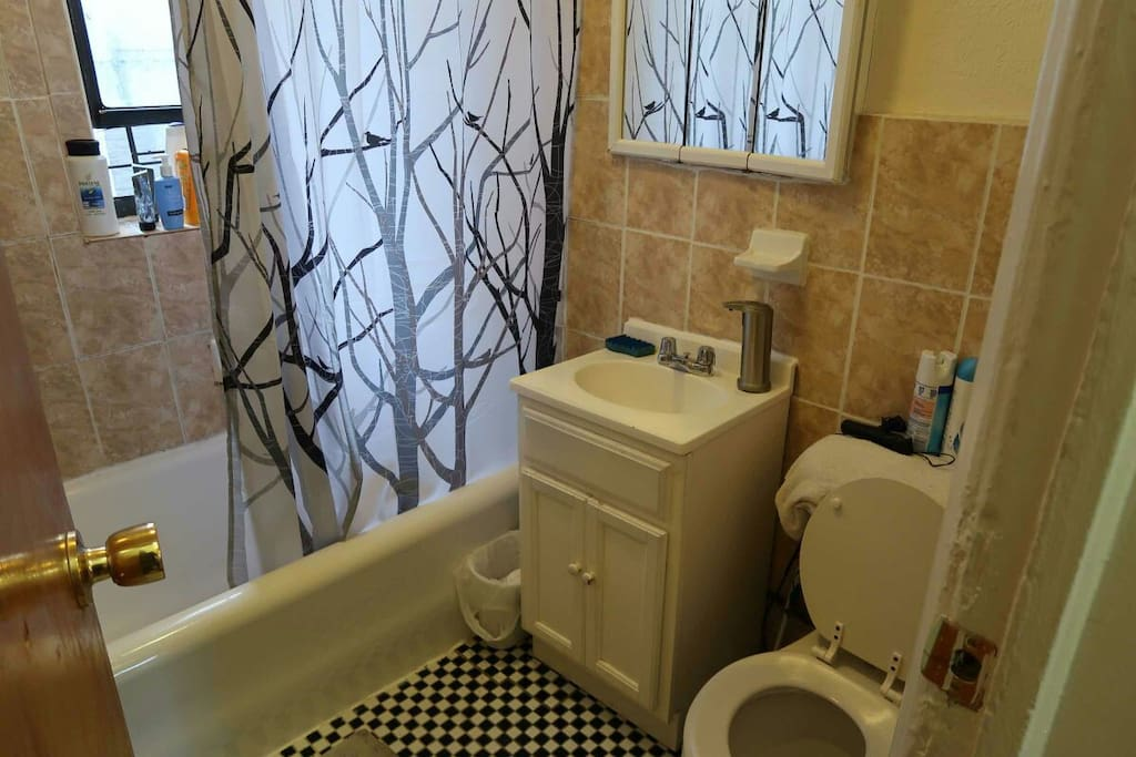 Bathroom that's always kept clean with automatic soap dispenser, floor mats, towels