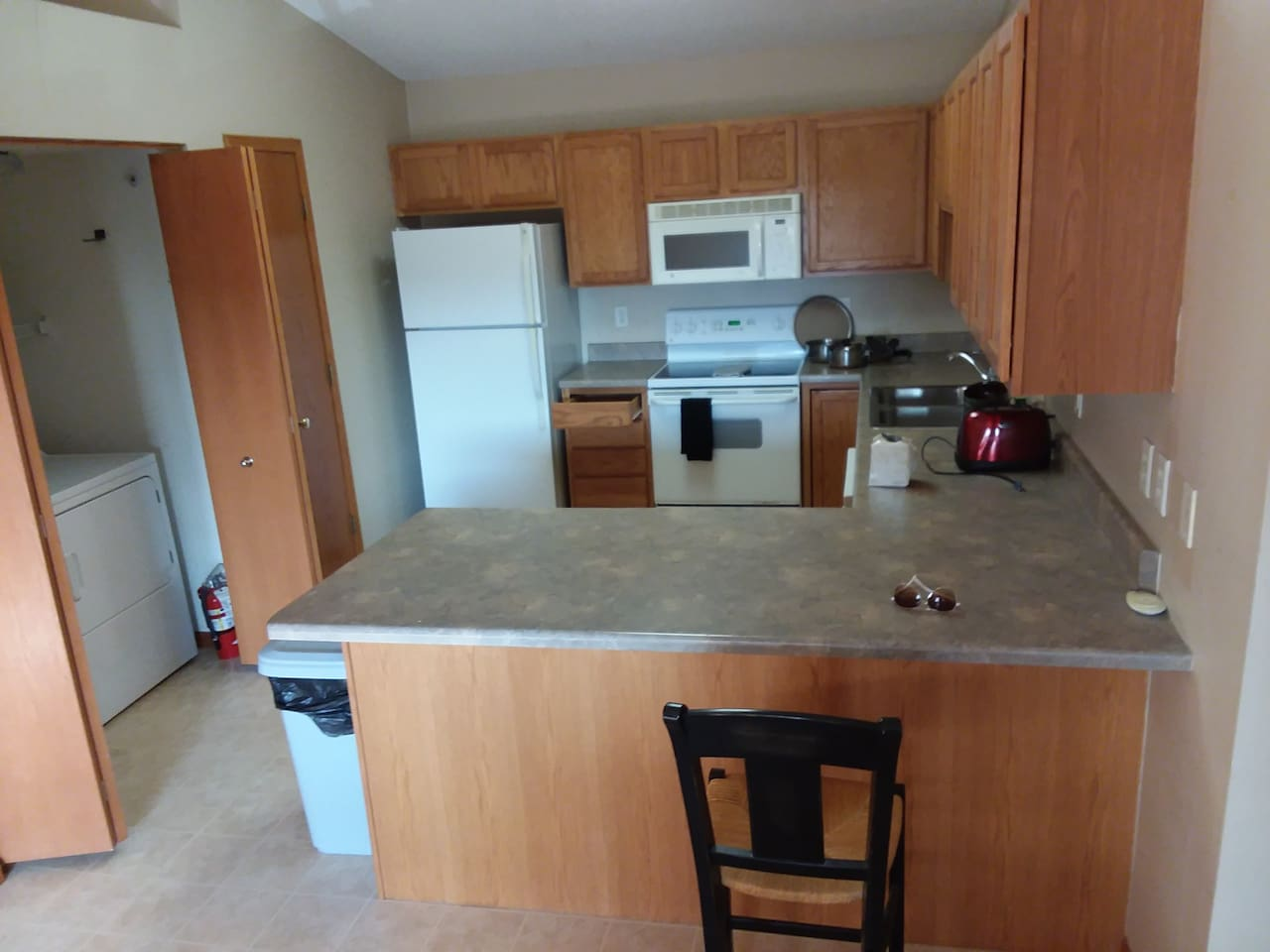 full kitchen with breakfast bar and pots and pans and silverware and dishes, toaster, full fridge, and washer and dryer,