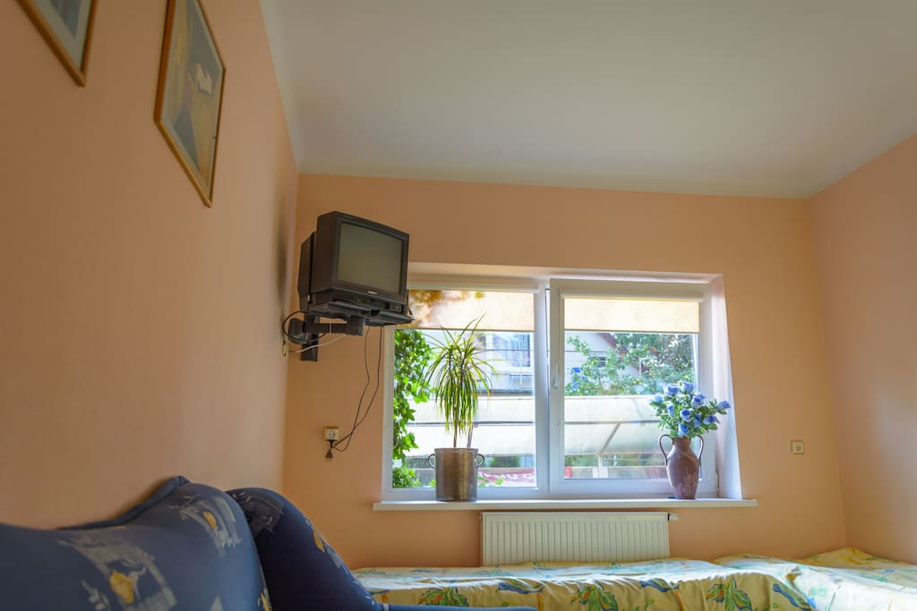 Room for four with one double sofa bed and two single beds, TV, table, chair, wardrobe.
