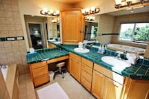Large master bathroom with his & her sinks, vanity area, two person Jacuzzi tub and dual head tiled shower.