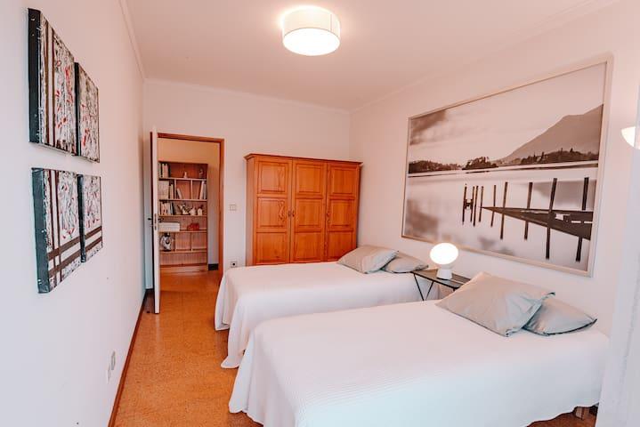 Quarto com duas camas de solteiro com varanda e vista de mar