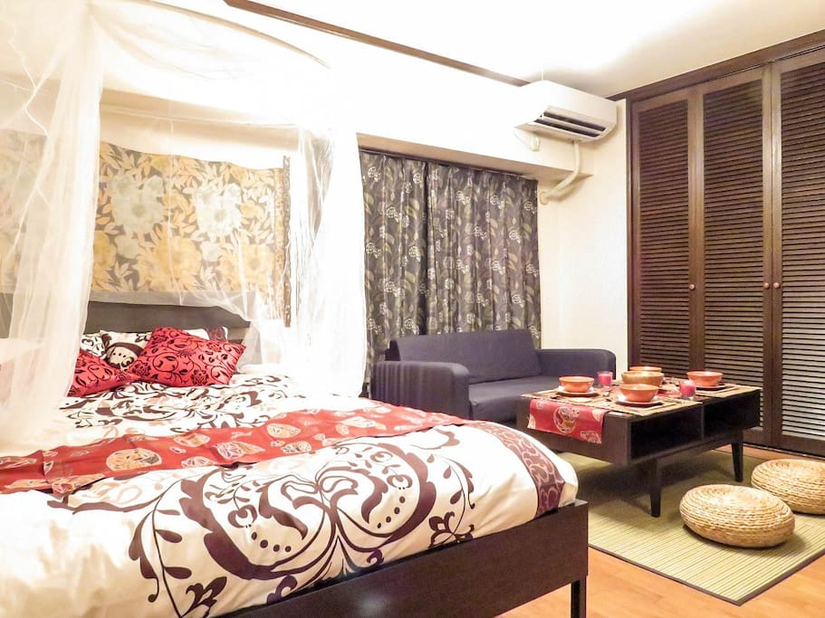 The entire view of the bed room. There are a double bed and a semi sofa bed, low table.