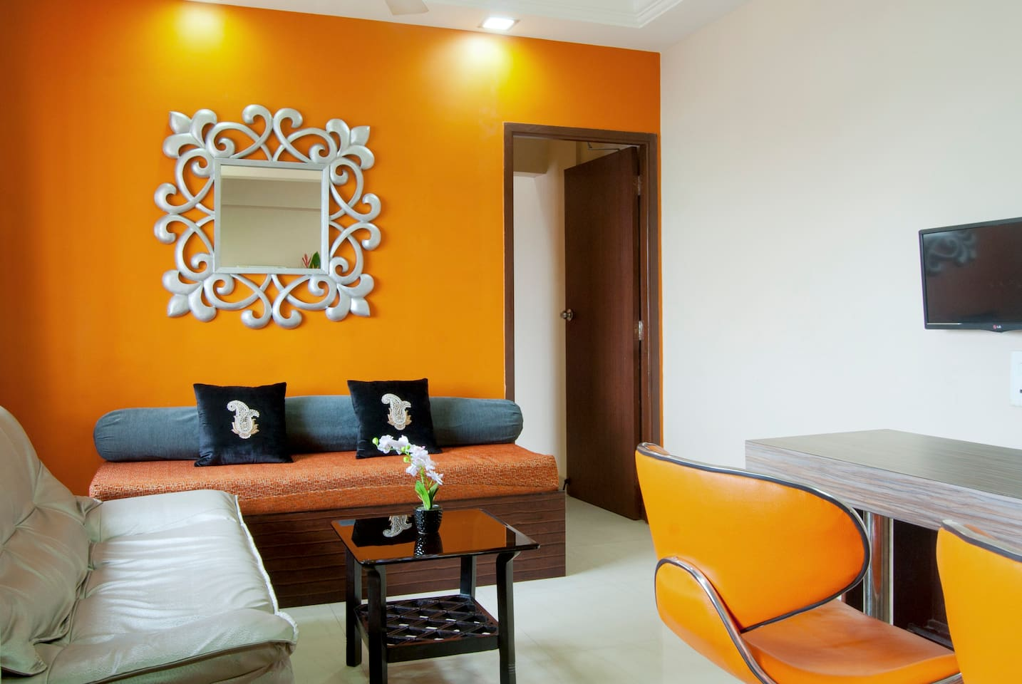 Colurful, bright Living room with an eat-in kitchen dining coounter,  & flat screen TV
