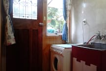 Laundry with back door and washing machine.