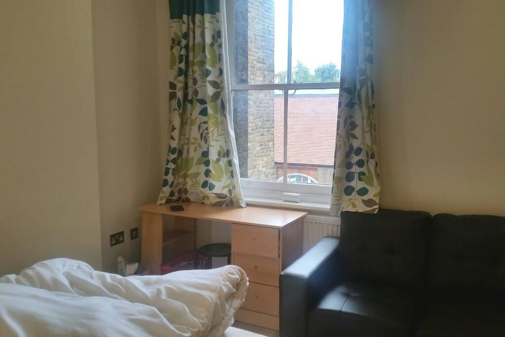 Une grande fenêtre juste en fasse du lit et un canapé