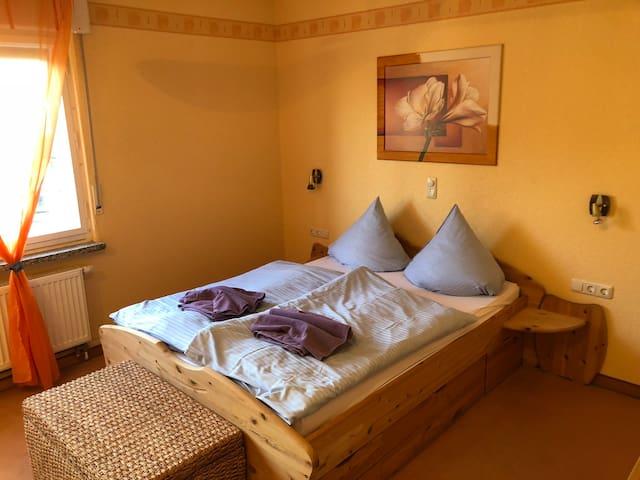 Schlafzimmer mit Doppelbett und Wäschetruhe, optional mit Kinderbett, Großer, leiser Deckenventilator.