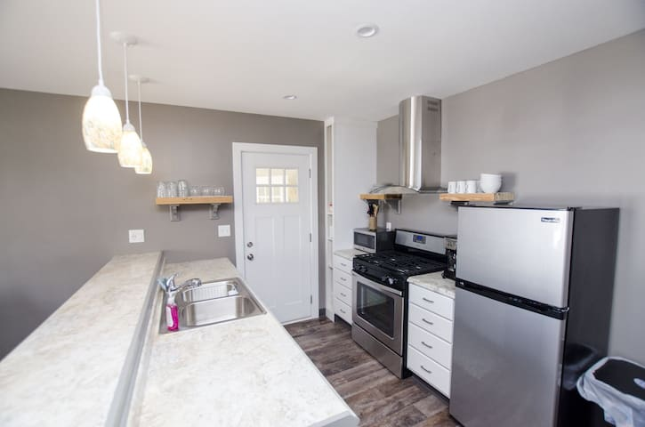 There are two identical kitchens with all stainless appliances a microwave, dishwasher and Kureig coffee maker.