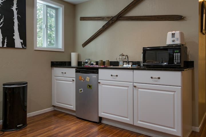 Kitchenette with a mini fridge, microwave, French press, hot water maker and toaster, plates and flatware in the cabinets.
