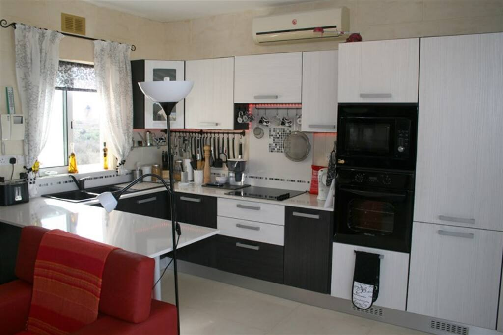 Kitchen fully equipped with electric hob, oven,  microwave and fridge freezer