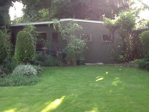 Houten bungalow in groene tuin