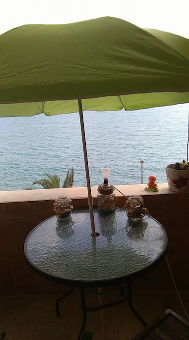 Our little table with a nice shade, perfect to read a book or chill, with the sea view