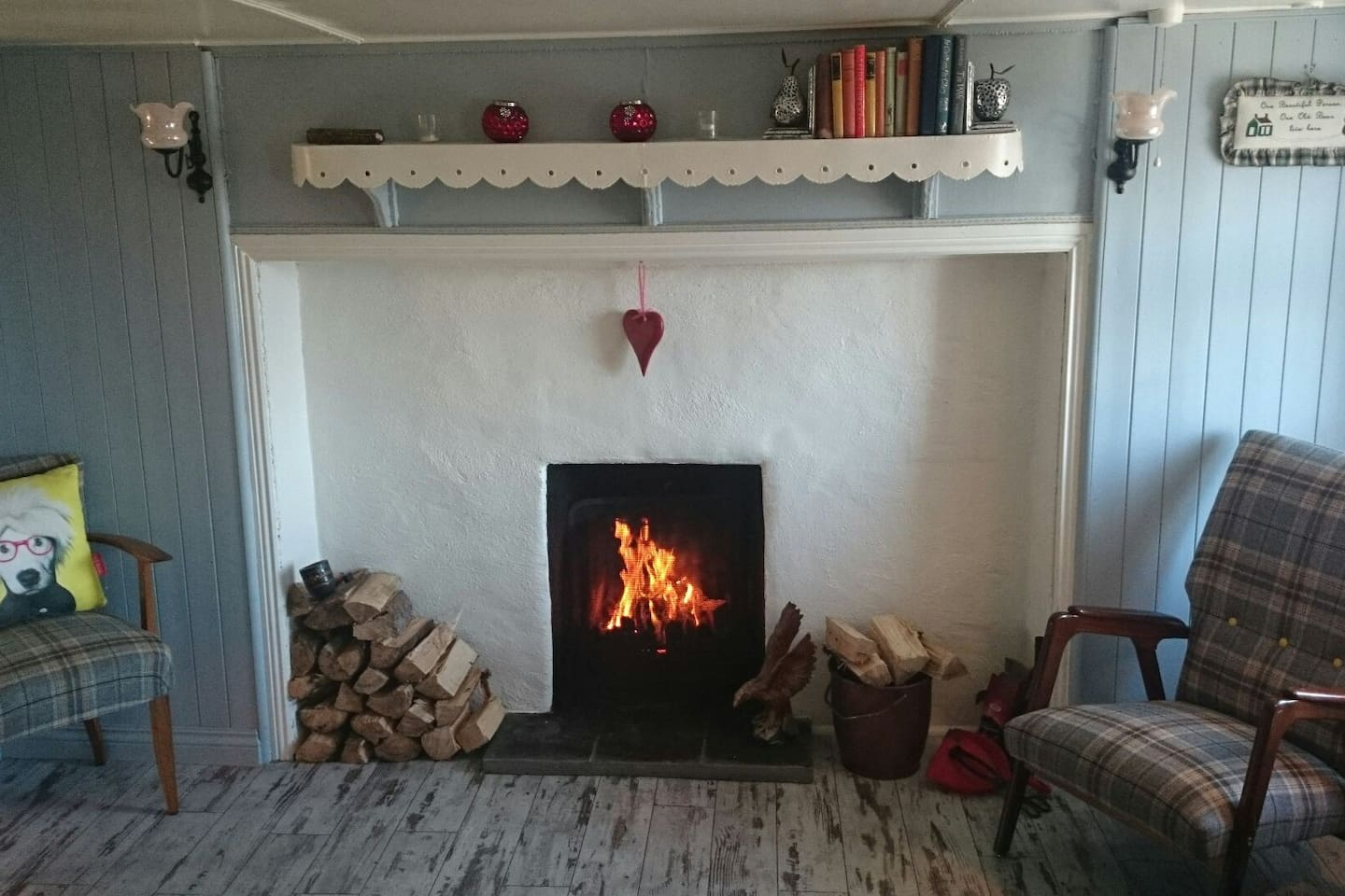The original fireplace in the main room with a roaring fire and 2 vintage chairs to sit on either side of the fire.