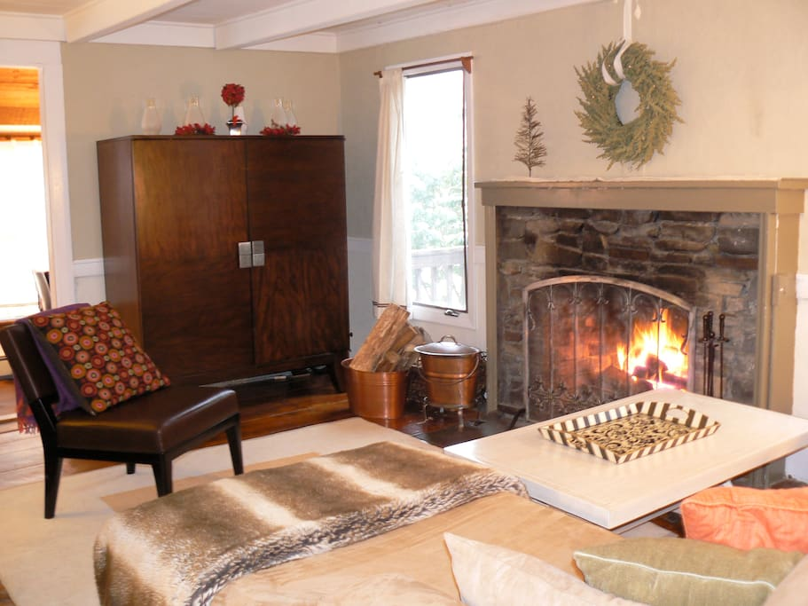 Main floor living room with original artisan fireplace.
