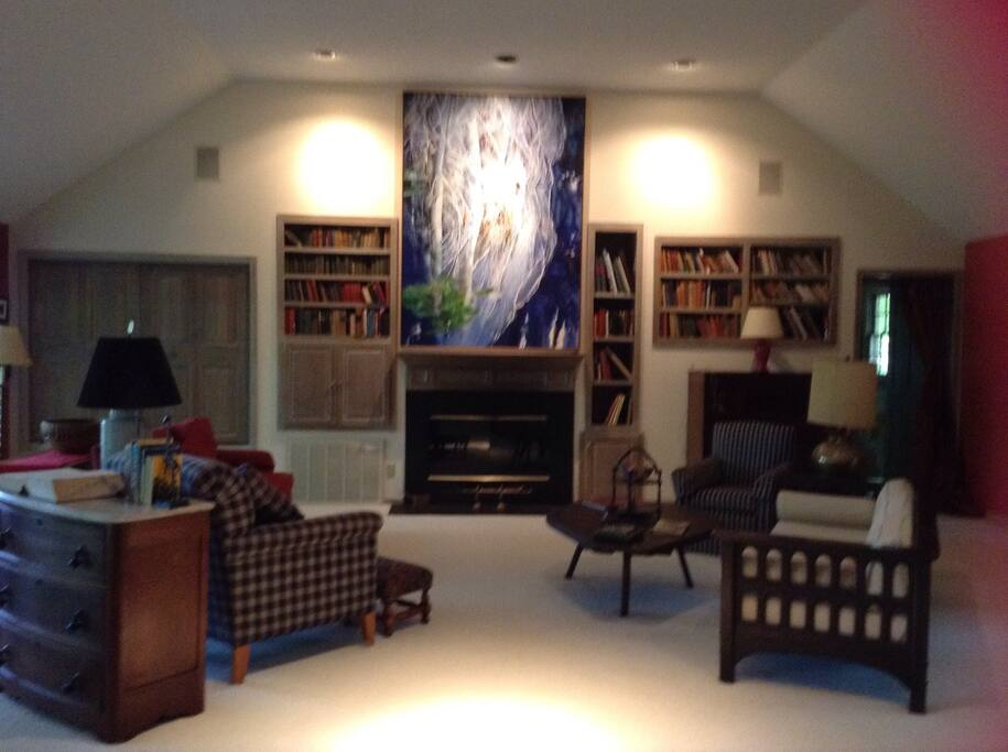Your cozy living room with high ceiling, gas log fireplace and TV behind cabinet doors left of FP