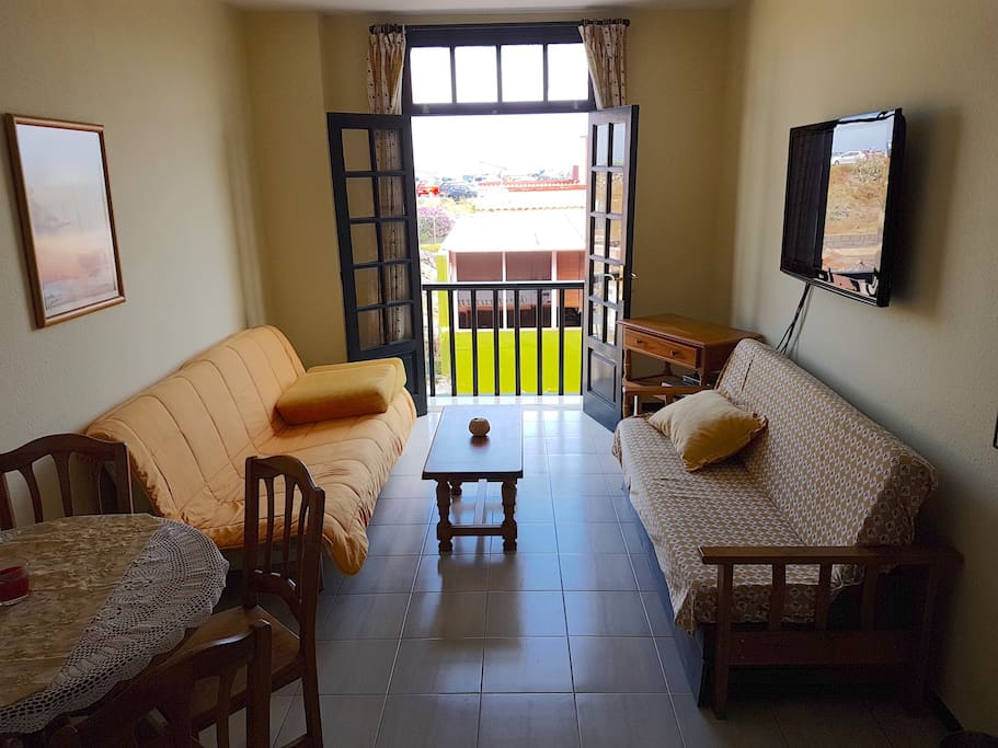 Living area from a different view, with small balcony overlooking street