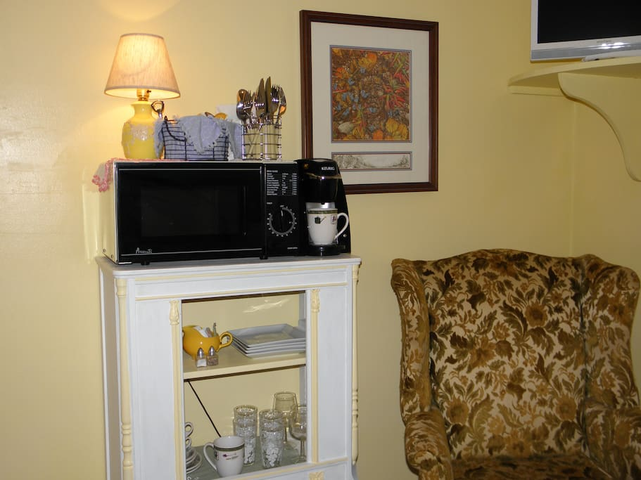 The room includes a Keurig, water cooler, microwave, and small refrigerator.