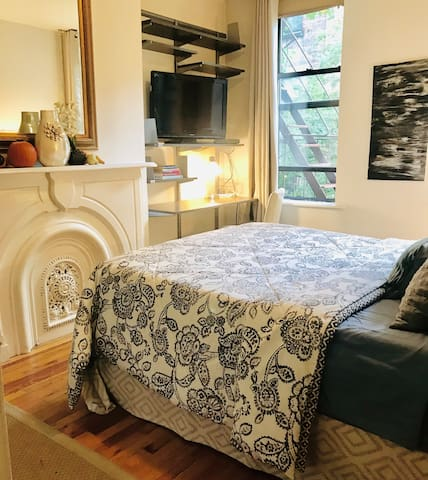 Master bedroom and fire place, with comfy queen bed, overlooking beautiful garden area.