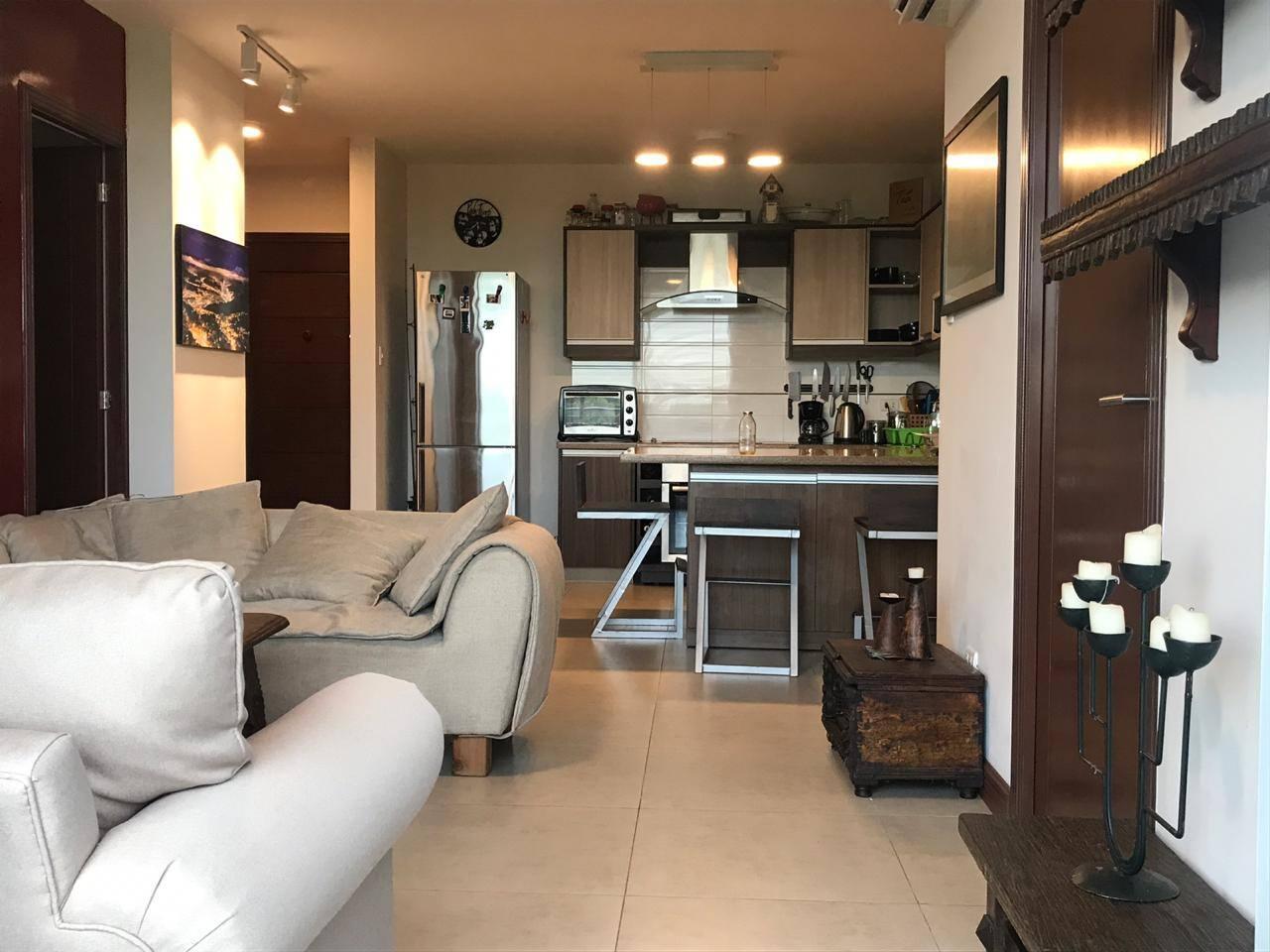 Sala de estar y cocina con isla con ruedas para ser utilizada como mesa también