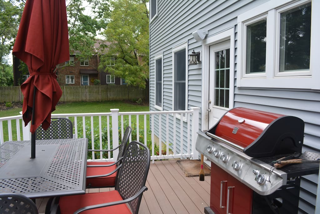 Backyard deck with table for 6 and gas grill.