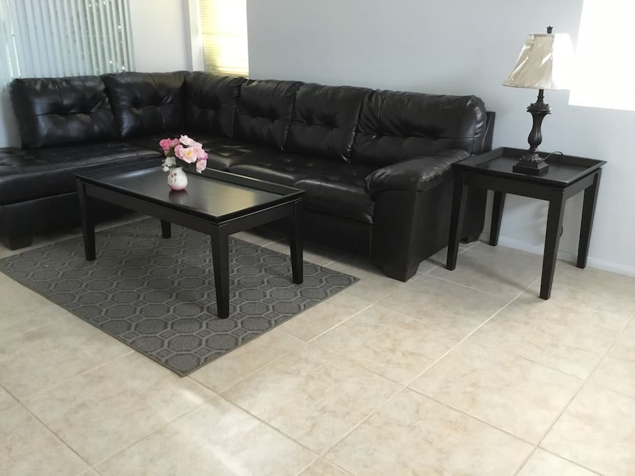 Large living room with new Ashley Furniture sectional leather sofa and coffee and end tables