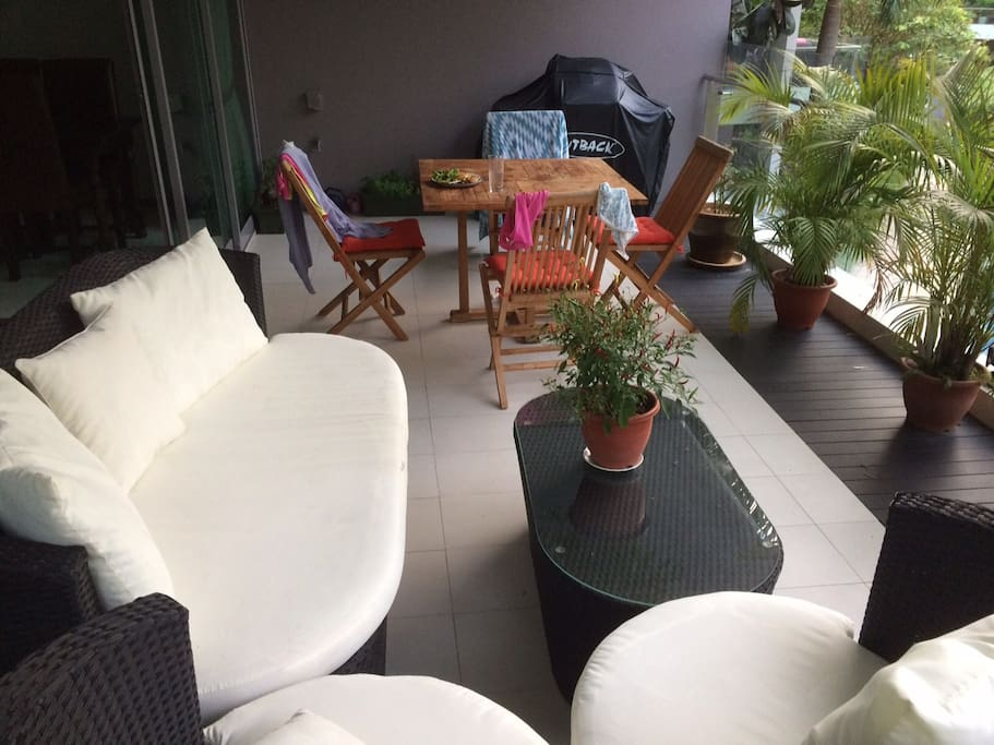 Large balcony with bbq, table and couch area