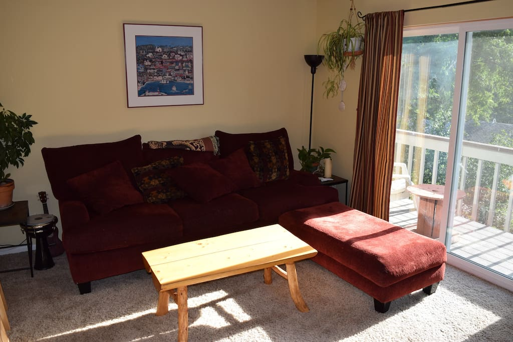 The living room has a big sliding glass door that lets in bright morning light.