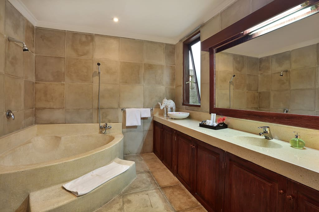 Spacious bathroom with bathtub and shower overhead