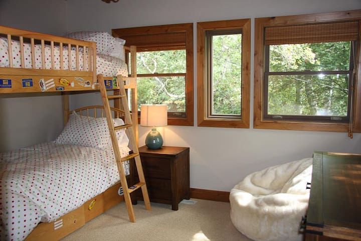 Bunk room with large walk-in closet and a chest of drawers