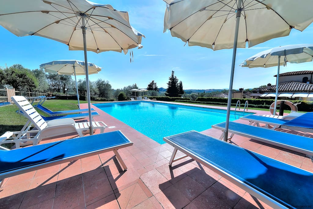 our swimmingpool with sun-beds and umbrellas