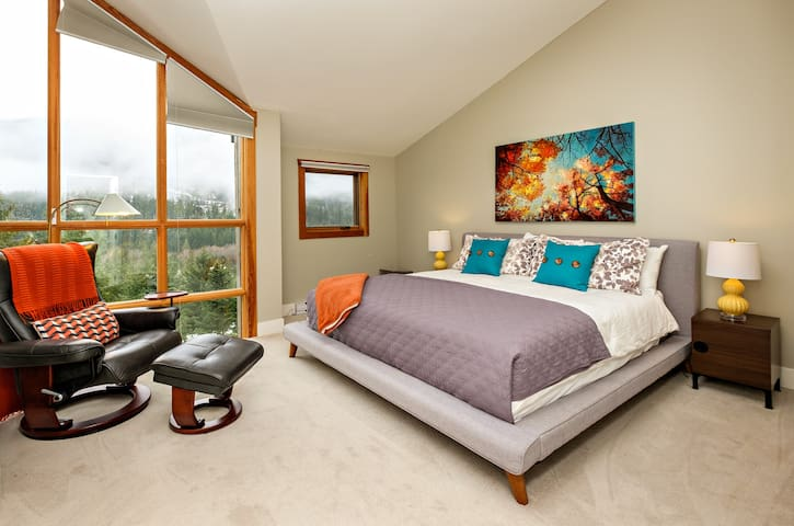 The master bedroom with king size bed.  There is a TV behind the black chair.  This bedroom has an ensuite bathroom and double closet.  Exceptional views of the mountains. This bedroom is on the foruth level.