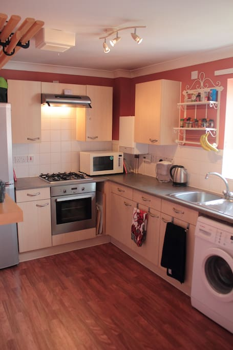 large open kitchen with oven, microwave, fridge, freezer, washing machine etc.