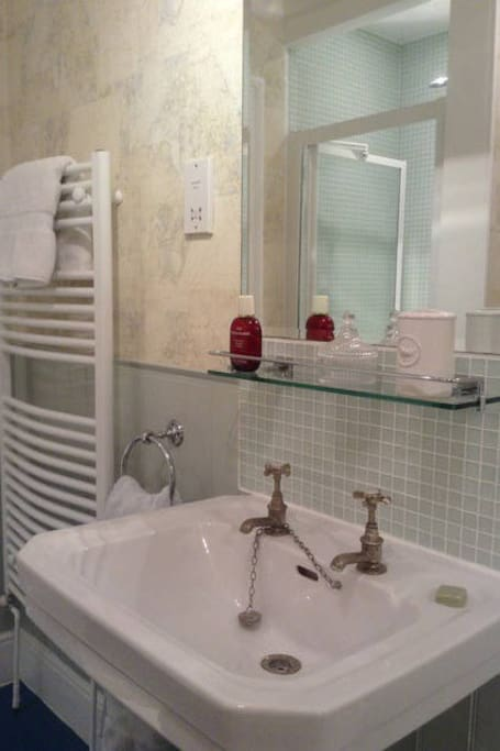 The newly decorated bathroom with power shower, bath and heated towel rail.
