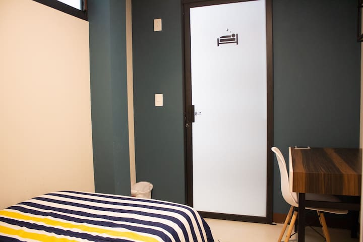 Habitación con cama individual y escritorio