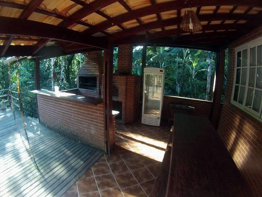 Área gourmet com churrasqueira, forno e fogão a lenha e freezer vertical.