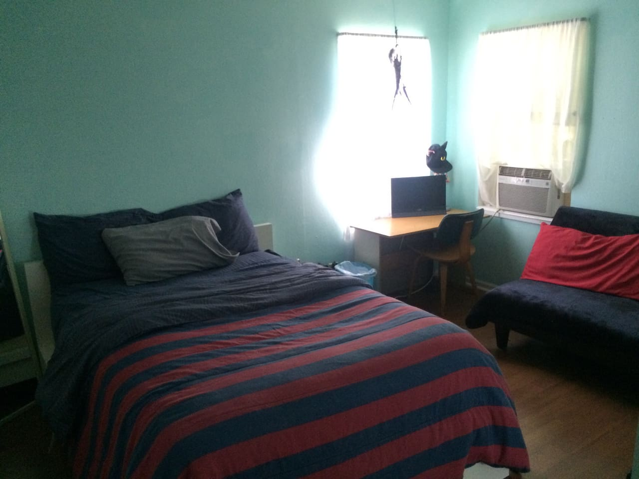 Picture of guest room. One full size bed and one futon.