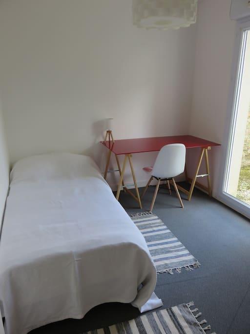 une chambre avec un lit une personne avec bureau et penderie