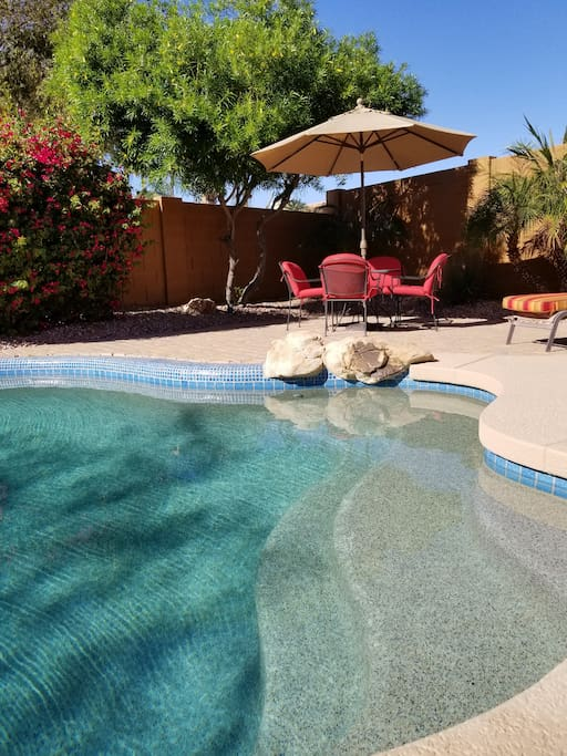 Pool deck with 10ft patio umbrella and chairs.