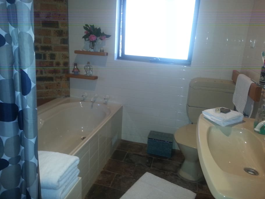 A clean bathroom with separate shower and bath.