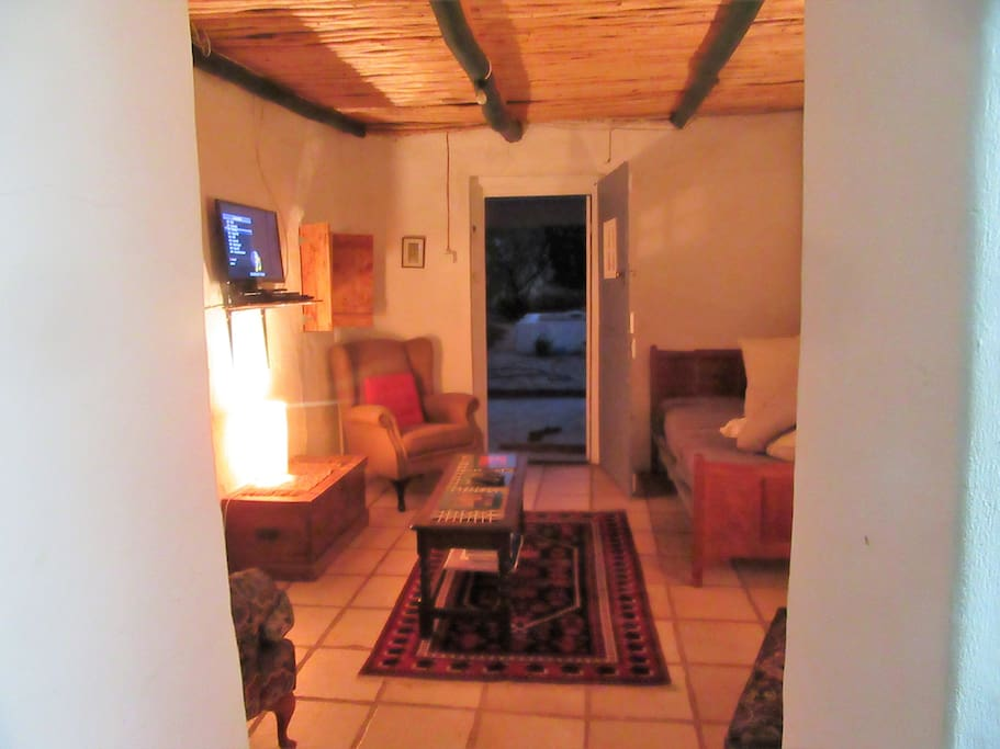 The small lounge has three armchairs and bed.
