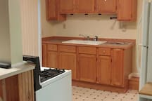 Kitchen has a full size refrigerator and has stove and is stocked with plates, silverware, glasses, pots and pans,utensils, microwave, coffee maker.  Small rolling island for additional storage and prep space.