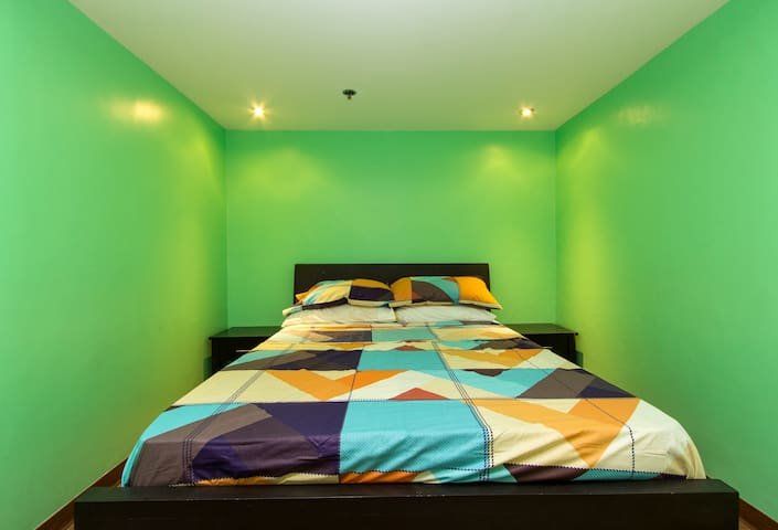 Master's bedroom with 1 queen sized bed with one aircon, lampshade, closet with hangers and a bathroom