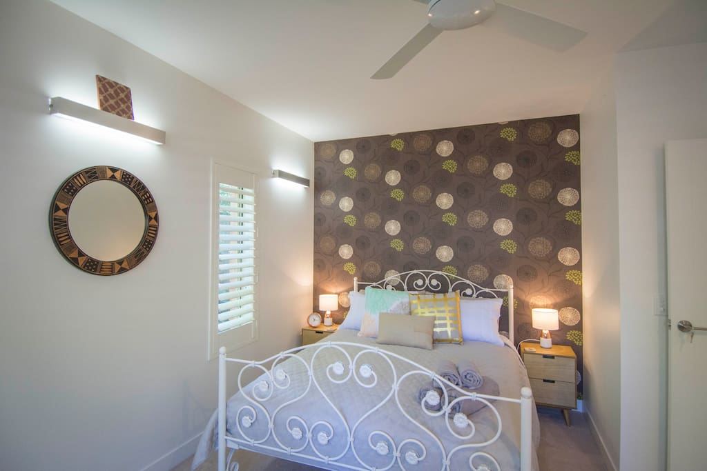 The spacious main bedroom features a Queen size bed and luxurious bedding.