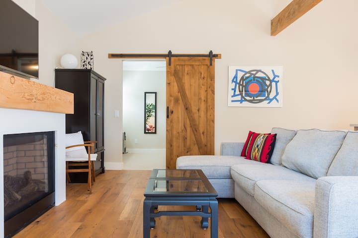 The living area feels light and spacious with high-ceilings, rustic wood beams and gas fireplace. The barn door provides privacy to the bedroom. The armoire is stocked with hangers and extra pillows. Stream movies, shows or music on the flatscreen TV