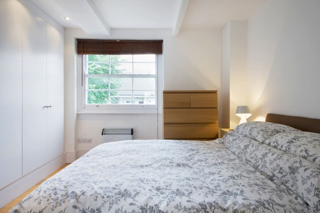 Double bed with large mirror and window letting in morning sun