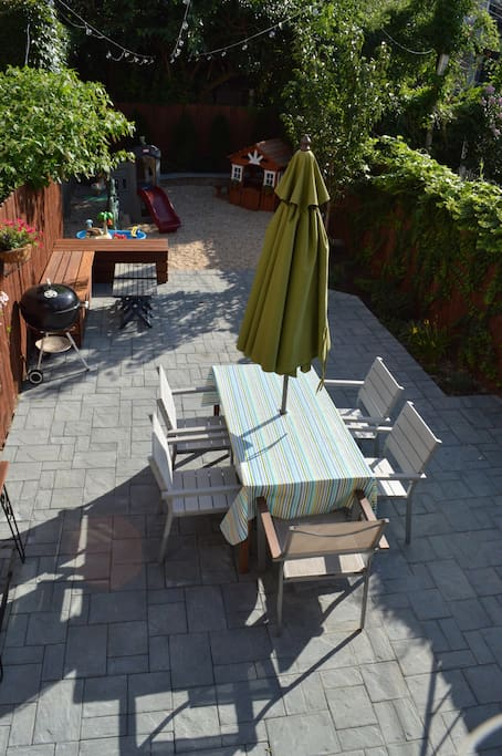 The backyard, great for relaxing and fun. There's a table and umbrella, extra seating, and a kids play area