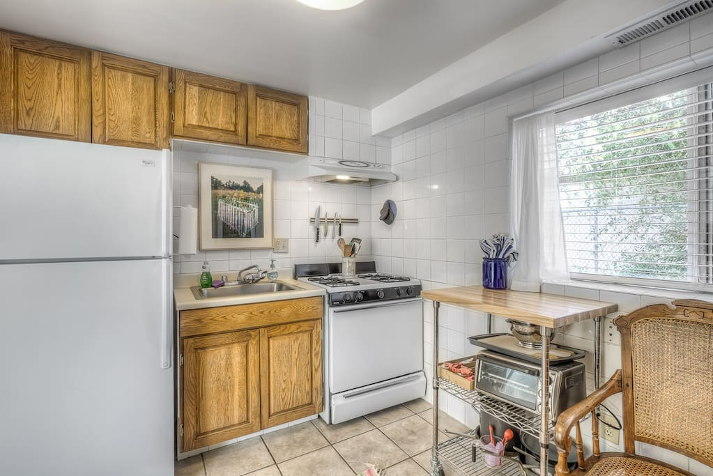 Kitchen with full size refrigerator, gas range, and all cooking and plate ware.